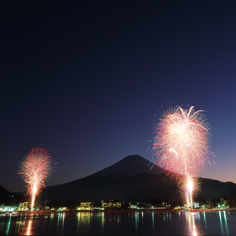 荘厳な富士山を背景に美しい花火が打ち上がる